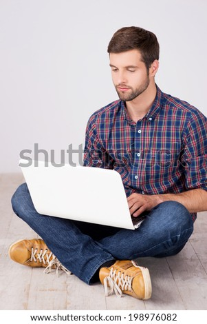 Casual man working on laptop. Handsome young man working on laptop while sitting on hardwood floor - stock photo