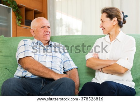 Casual mature couple having serious talking in  room