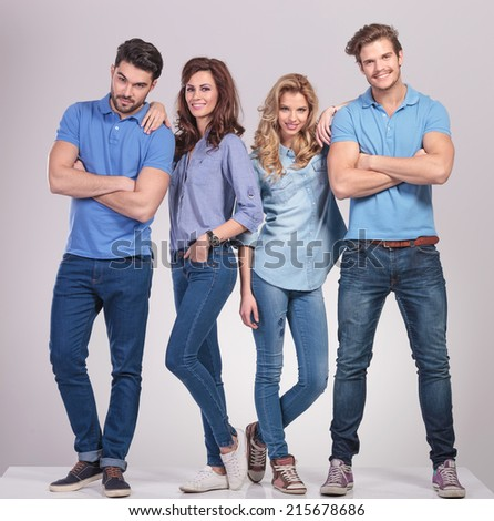 casual men standing with hands crossed and women lean on them on grey studio background