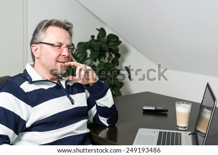 Casual middle aged man working from home on laptop computer with phone and coffee - stock photo