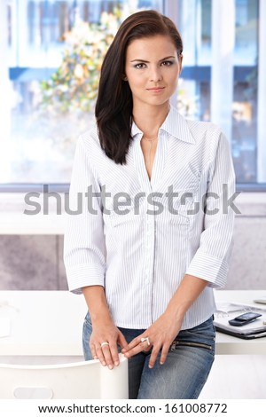 Casual office worker standing in office by desk, looking at camera.