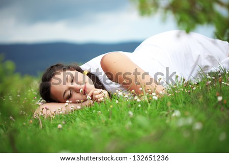 Casual outdoor portrait of young beautiful woman resting at spring nature