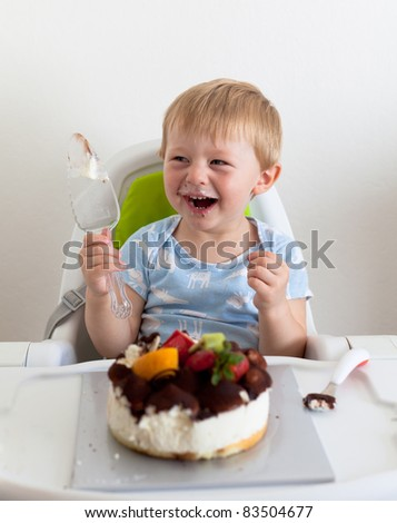 Casual portrait of a two-yer-old eating a cake - stock photo