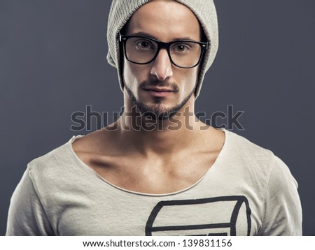 Casual portrait of a young man wearing a cap, over a blue background - stock photo