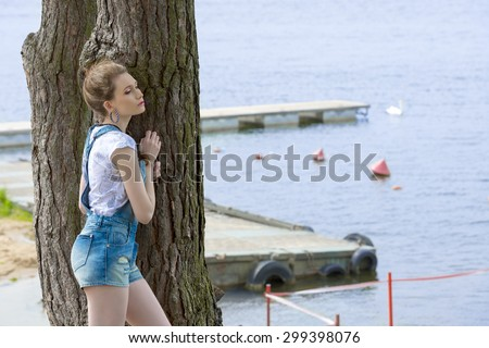 casual pretty woman with denim overalls and t-shirt posing with relaxed pose outdoor near tree with blue sea water on background  - stock photo