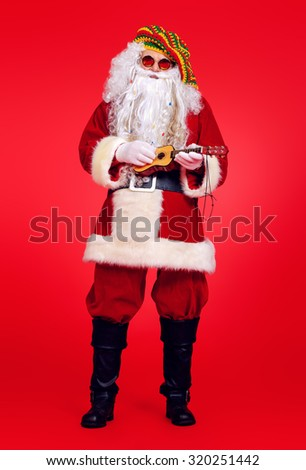 Casual Santa Claus hippie playing ukulele over festive red background. - stock photo