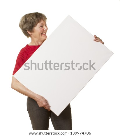 Casual senior businesswoman smiling happily at the blank sign or placard she is holding crockedly, isolated on white.