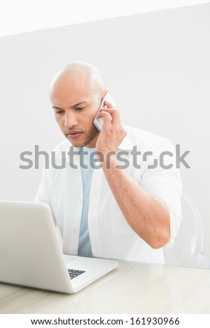 Casual serious young man using cellphone and laptop at desk against white background