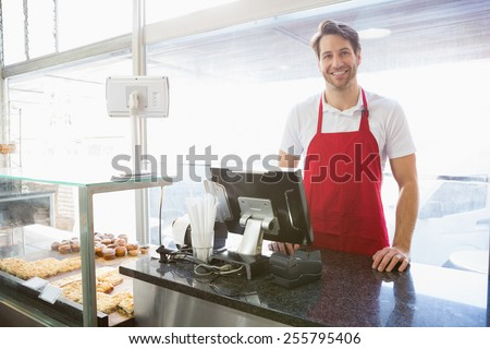 Casual server posing behind the counter at the bakery - stock photo
