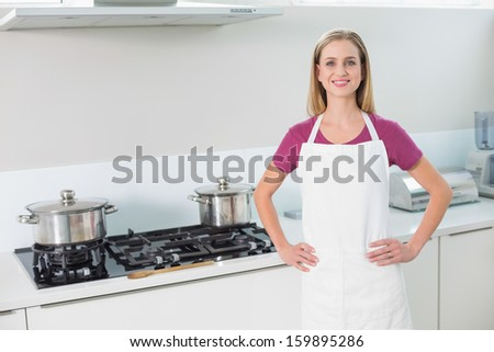 Casual smiling blonde standing next to stove in bright kitchen - stock photo