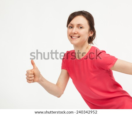 Casual smiling young woman showing thumbs up sign on neutral background - stock photo