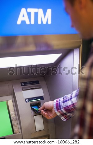 Casual student withdrawing cash at an ATM - stock photo