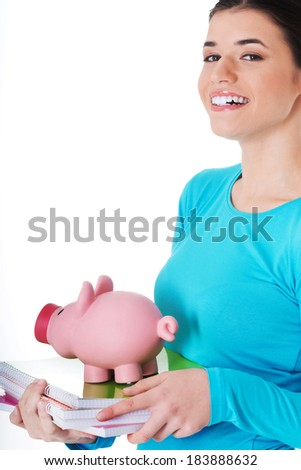 Casual student woman holding workbook and piggy-bank. Isolated on white.  - stock photo