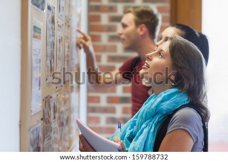 Casual students looking at notice board in college - stock photo