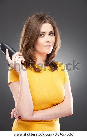 Casual style woman portrait. Isolated over gray background. girl using the mobile phone for conversation holding it the hand - stock photo