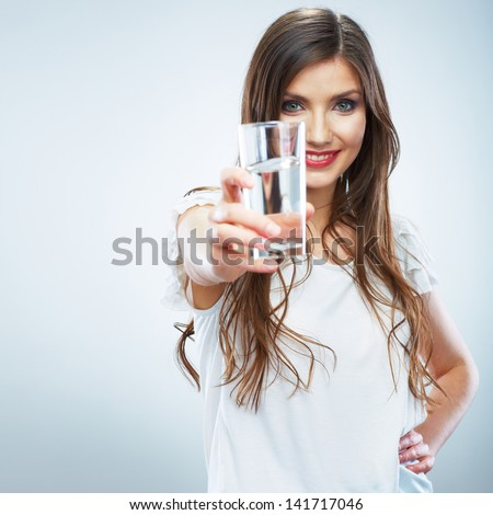 Casual style young woman posing on isolated studio background, hold water glass. Beautiful girl portrait. Female model poses. - stock photo