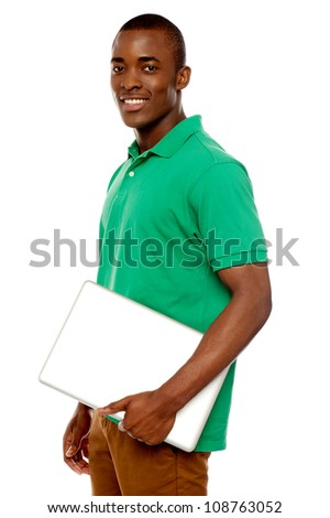 Casual teenager carrying laptop and looking at camera - stock photo