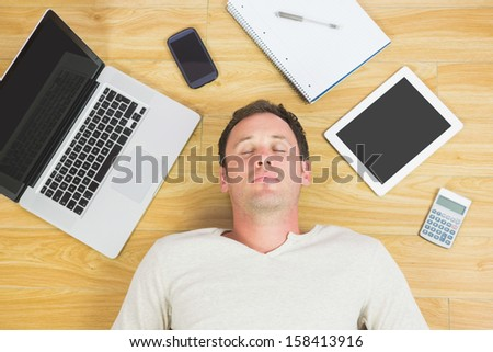 Casual tired man lying on floor in bright room - stock photo