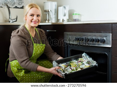 Casual woman cooking fish  in oven at home kitchen