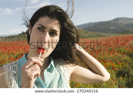 Casual woman eating candy at outdoors with sunlight - stock photo