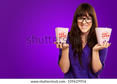 Casual Woman Holding Popcorn Container Isolated On Purple Background - stock photo