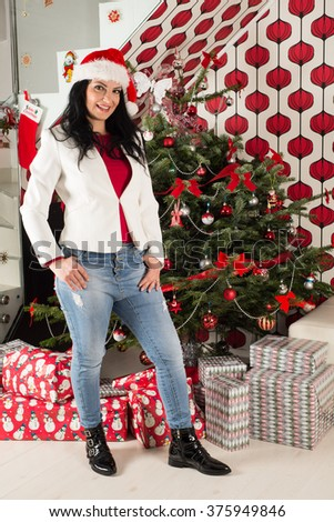 Casual woman posing in front of natural Christmas tree with presents