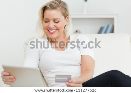 Casual woman sitting on the sofa using a tablet pc on the sofa - stock photo