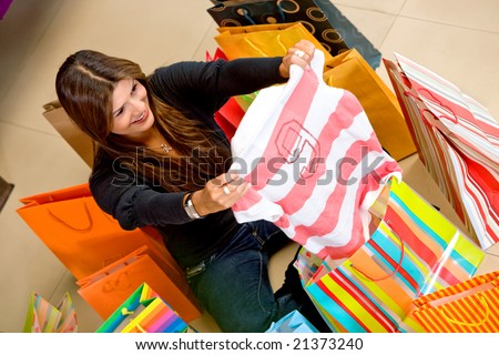 casual woman smiling in a store shopping for gifts - stock photo