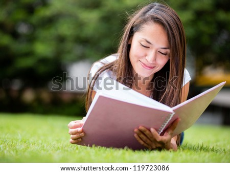 Casual woman studying outdoors laying on the grass - stock photo