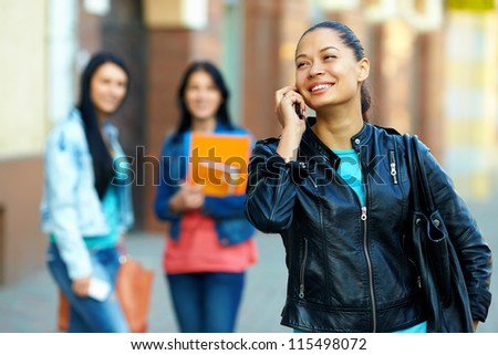 casual woman talking on the mobile phone, while walking the street - stock photo