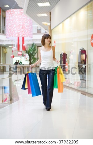 Casual woman walking with shopping bags in a mall