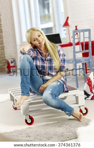 Casual young blonde woman sitting at modern home, smiling happy. Full size. - stock photo