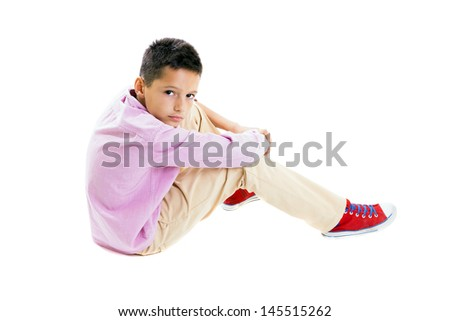 Casual young boy portrait, sitting on the floor, holding his knees with both hands, full lenght body, isolated on white. - stock photo