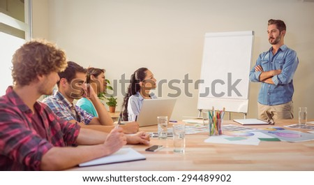 Casual young businessman giving a presentation to his colleagues - stock photo