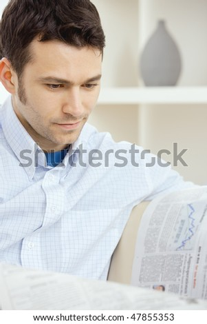 Casual young businessman reading business news, sitting on couch at home, looking at newspaper.