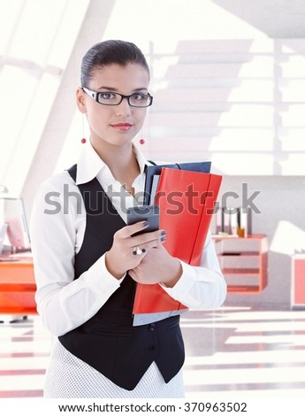 Casual young caucasian female secretary wearing glasses standing with folders and mobile phone in hand at bright office. Looking at camera, copyspace. - stock photo