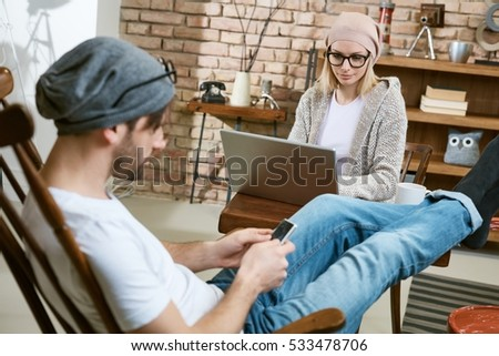Casual young couple sitting at home, using laptop and mobile, both wearing cap and glasses.