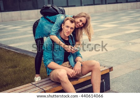 Casual young couple using smartphone in a city. - stock photo