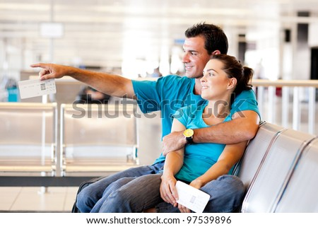 casual young couple waiting for flight at airport - stock photo