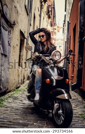 Casual young foman in jeans and leather jacket sitting on scooter between two houses and holding her hairs. - stock photo