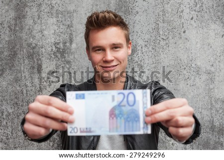 Casual young guy holding 20 euro note - stock photo
