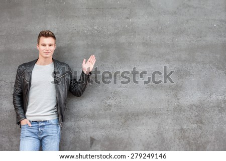 Casual young guy pointing to the side - stock photo