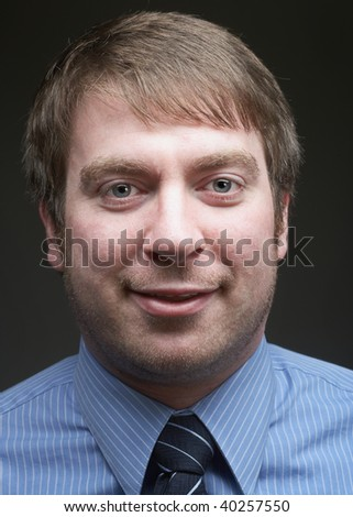 Casual young handsome businessman closeup on dark background - stock photo