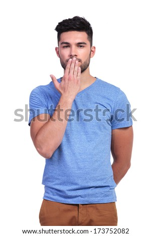 casual young man covering his mouth with his hand on white background - stock photo