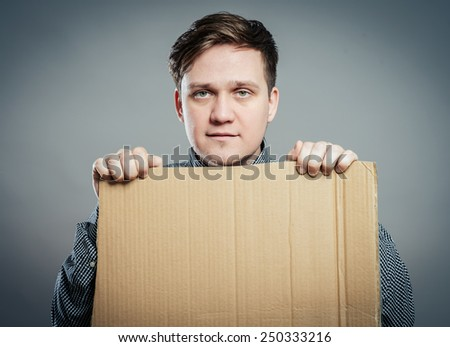 Casual young man holding a box isolated - stock photo