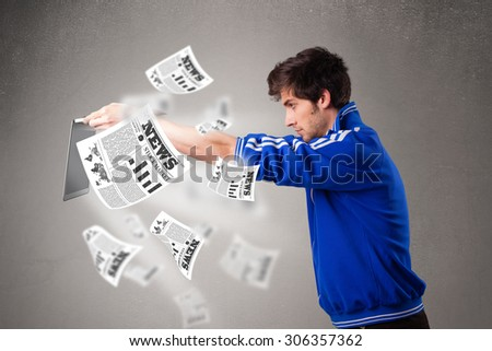 Casual young man holding a laptop and reading the explosive news - stock photo
