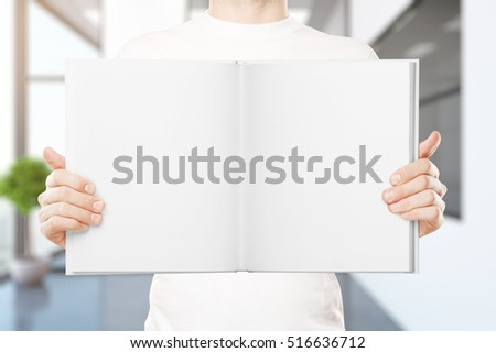 Casual young man holding empty open book in blurry interior. Mock up