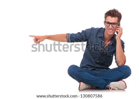 casual young man is pointing to his side while speaking on the phone and smiling to the camera from a seated position. isolated on white - stock photo