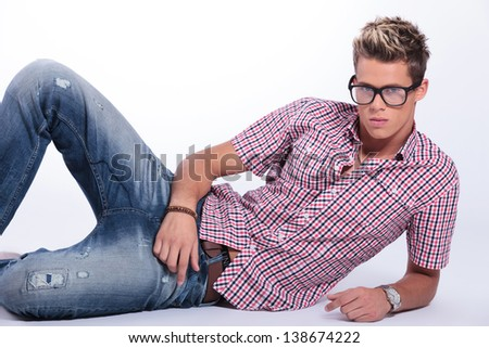 casual young man laying on the floor, on a side, looking at the camera with a serious expression. on gray background - stock photo
