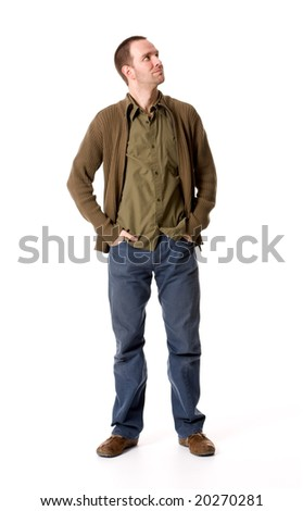 Casual young man looking up, hands in pockets - stock photo